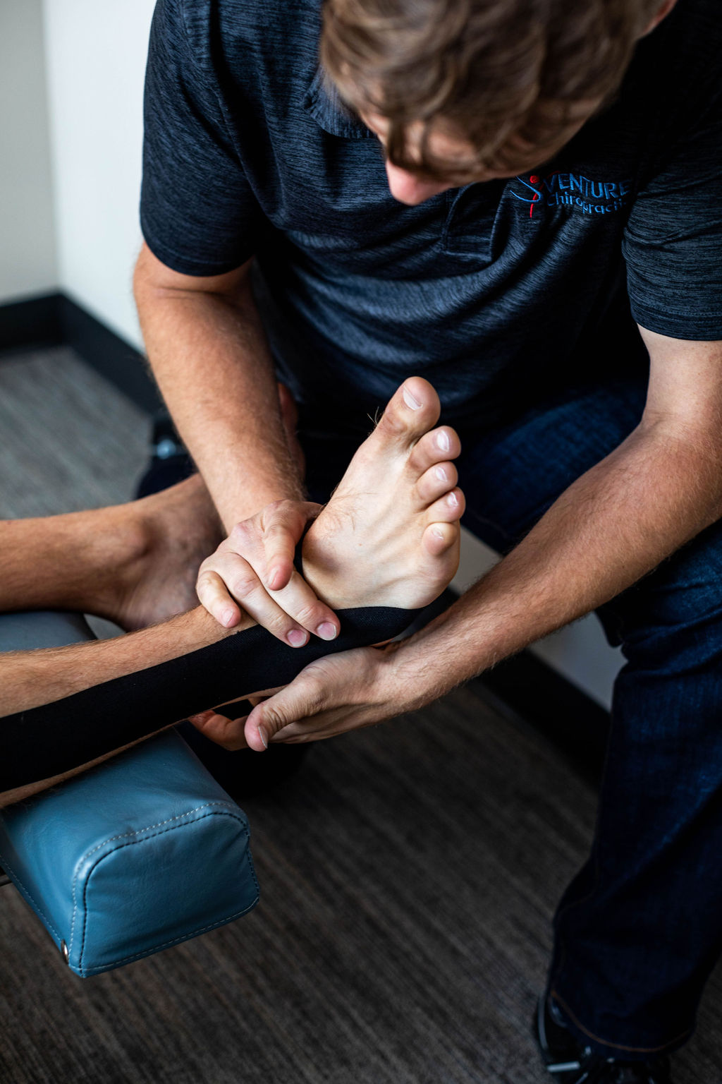 Dr. Chris is adjusting an athletes ankle to improve the motion after an ankle sprain.